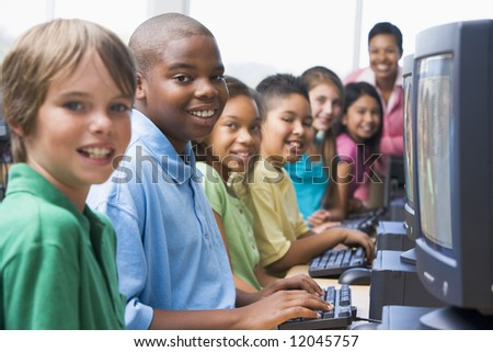 Elementary school computer class looking to camera