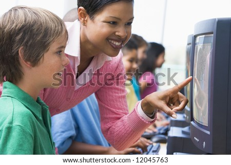 Elementary school computer class with teacher - stock photo