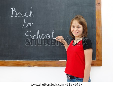 Elementary school girl writing Back to School on chalkboard - stock photo