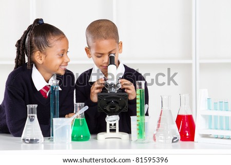 elementary school kids in science class using a microscope - stock photo