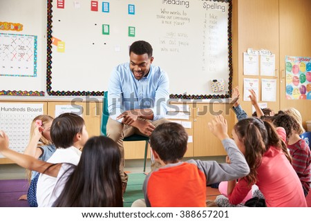 Elementary school kids sitting around teacher in a classroom - stock photo