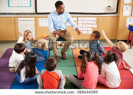 Elementary school kids sitting around teacher in a lesson - stock photo