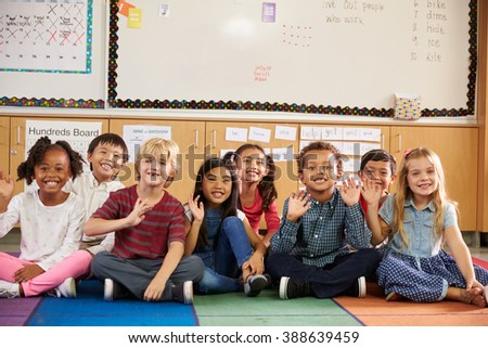 Elementary school kids sitting on classroom floor - stock photo