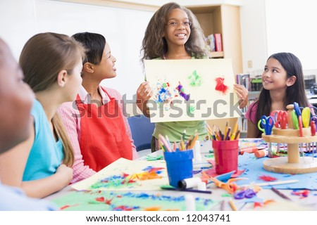 Elementary school pupil discussing picture with classmates - stock photo