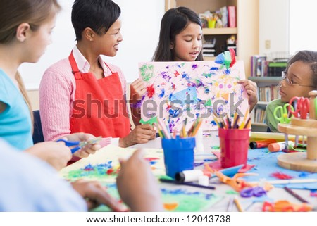 Elementary school pupil in art class showing picture to classmates - stock photo