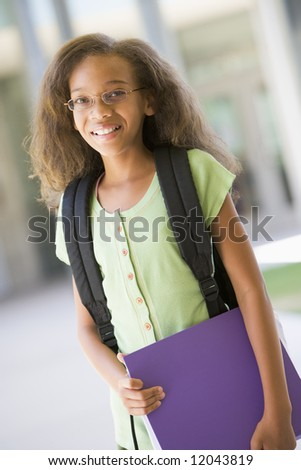 Elementary school pupil outside carrying file