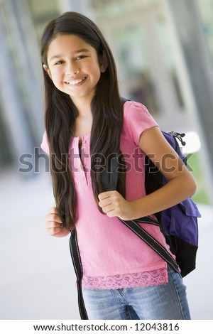 Elementary school pupil outside carrying rucksack - stock photo