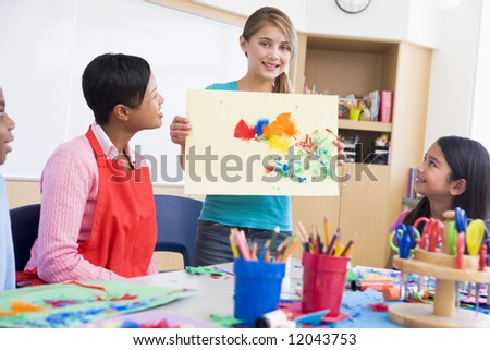 Elementary school pupil talking about picture in art class - stock photo