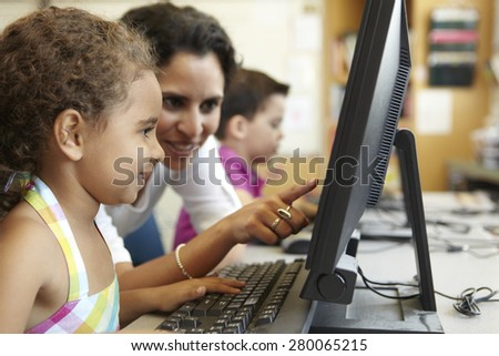 Elementary School Pupil With Teacher In Computer Class - stock photo