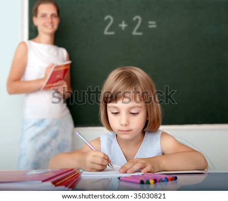 Elementary school pupil working at desk - stock photo