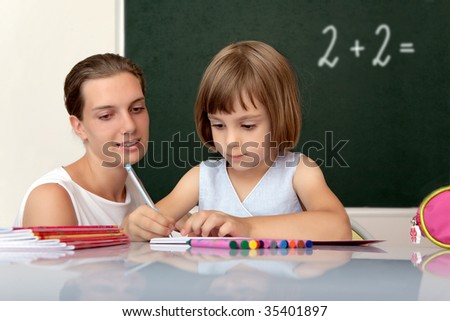 Elementary school pupil working under the supervision of a teacher