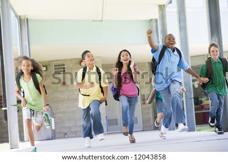 Elementary school pupils running outside together - stock photo