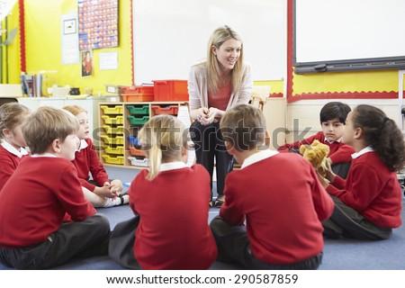 Elementary School Pupils Telling Story To Teacher - stock photo
