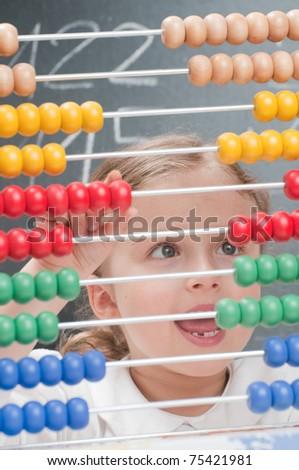 Elementary school - schoolgirl counting on abacus - stock photo