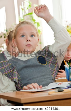 Elementary school. Schoolgirl in the classroom raises hand
