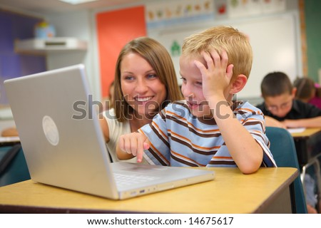 Elementary school student and teacher with laptop - stock photo
