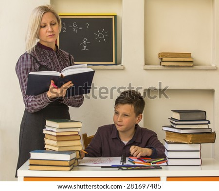 Elementary school student doing homework with the help of a tutor. - stock photo