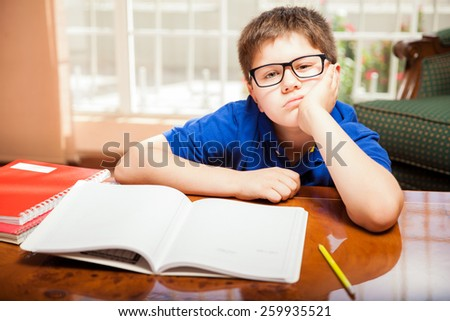 Elementary school student feeling bored and frustrated by his homework - stock photo