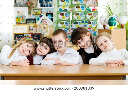 Elementary school student in a classroom near the blackboard points to the text. Education - stock photo
