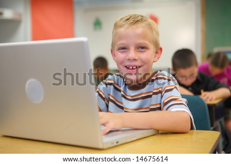 Elementary school student smiling at computer - stock photo