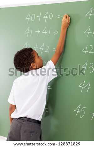 elementary school student writing maths answer on chalkboard - stock photo