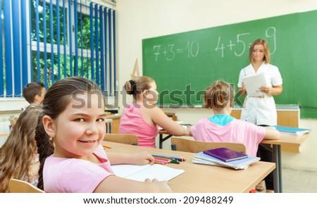 Elementary School Students at Classroom Desks - stock photo
