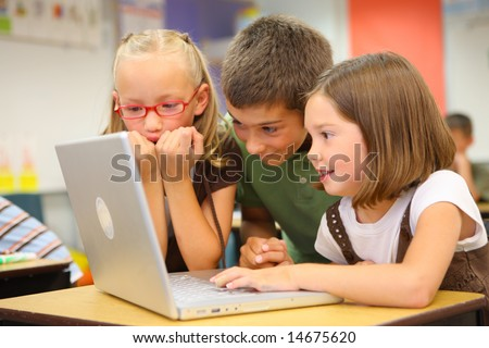 Elementary school students looking at computer - stock photo