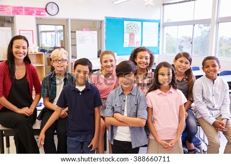 Elementary school teacher and her pupils in classroom - stock photo
