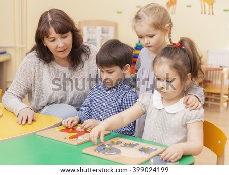 elementary school teacher collect puzzle with three pupils sitting at the table. One girl standing behind