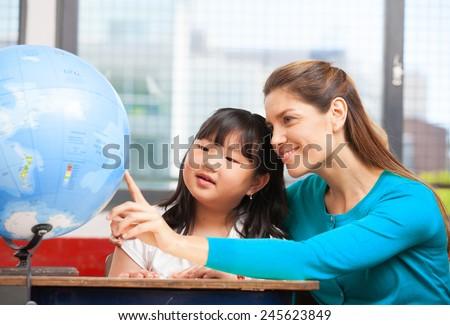 Elementary school teacher explaining Earth globe to asian female student. - stock photo