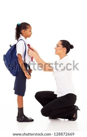 elementary school teacher helping schoolgirl fixing her tie