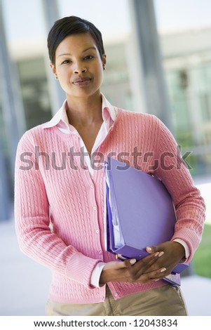 Elementary school teacher holding file - stock photo