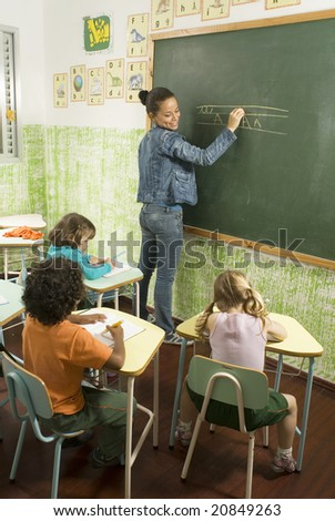 Elementary school teacher standing at a chalkboard writing as she smiles at her students writing at their desks. Vertically framed photo. - stock photo