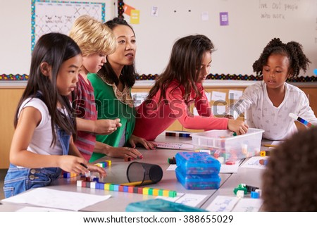 Elementary school teacher uses block play in class with kids - stock photo