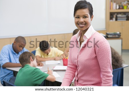 Elementary school teacher with pupils in background - stock photo
