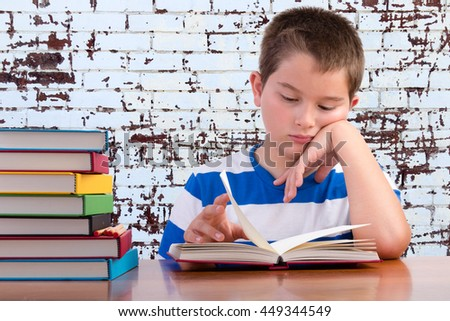 Elementary schoolboy focusing on his studies sitting at a desk in the classroom with a stack of colored textbooks reading from a book in front of him