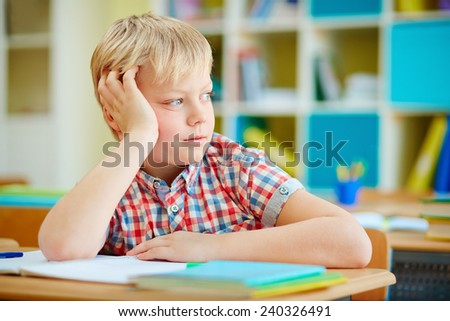 Elementary schoolboy sitting at lesson and looking aside - stock photo