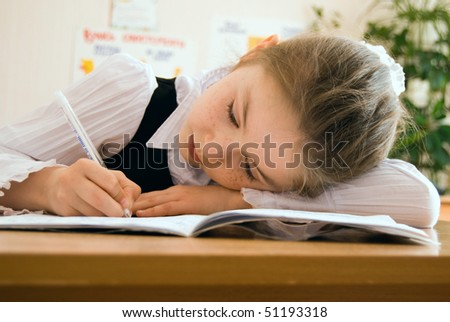 Elementary schoolgirl sitting in classroom and writing in the exercise book - stock photo