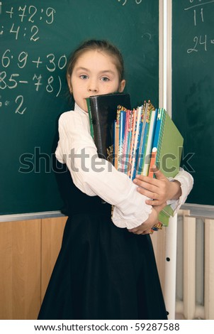 Elementary schoolgirl with books infront of  blackboard - stock photo