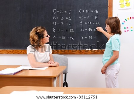 Elementary student solving equations at chalkboard while teacher looks at her
