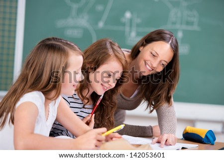 Elementary students listening to female teacher in school classroom - stock photo