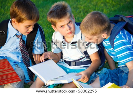 Elementary students reading book with interest