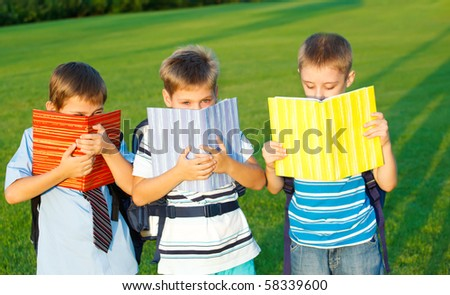 Elementary students with books in park - stock photo