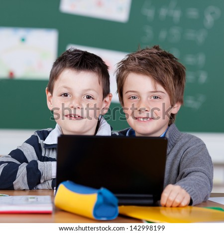 Elementary students working with laptop at the classroom - stock photo