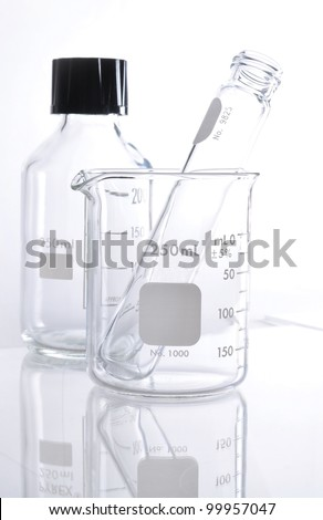 Elemeyer flask and glass tube for chemical science use in laboratory.
