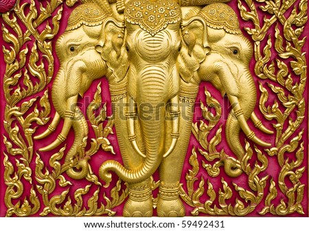 elephant carved gold paint on church door - stock photo