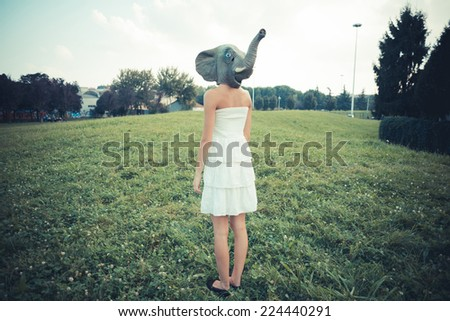 elephant mask beautiful young woman with white dress in the city - stock photo