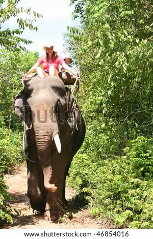 Elephant trekking. Mother and son on elephand back. - stock photo