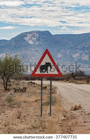 Elephants, Road sign standing beside road, Namibia - stock photo