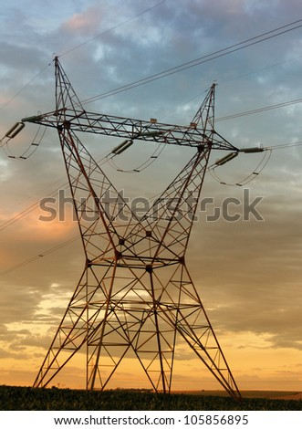 Eletricity tower providing energy distribution over sunset - stock photo